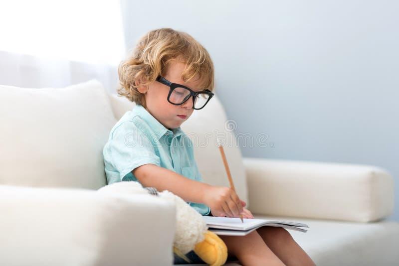 Chłopiec obsiadanie na leżance i rysunku zdjęcia stock