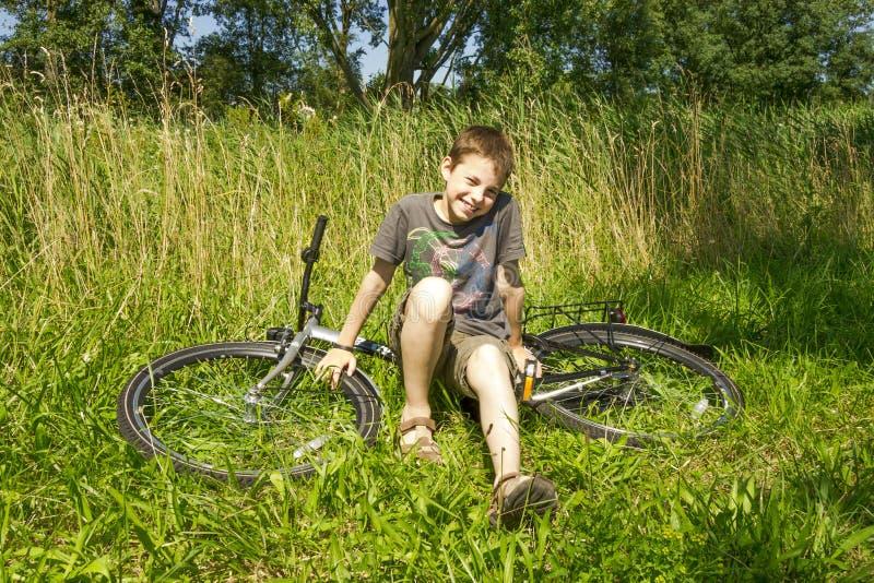 Chłopiec obsiadanie na rowerze w trawie zdjęcia stock
