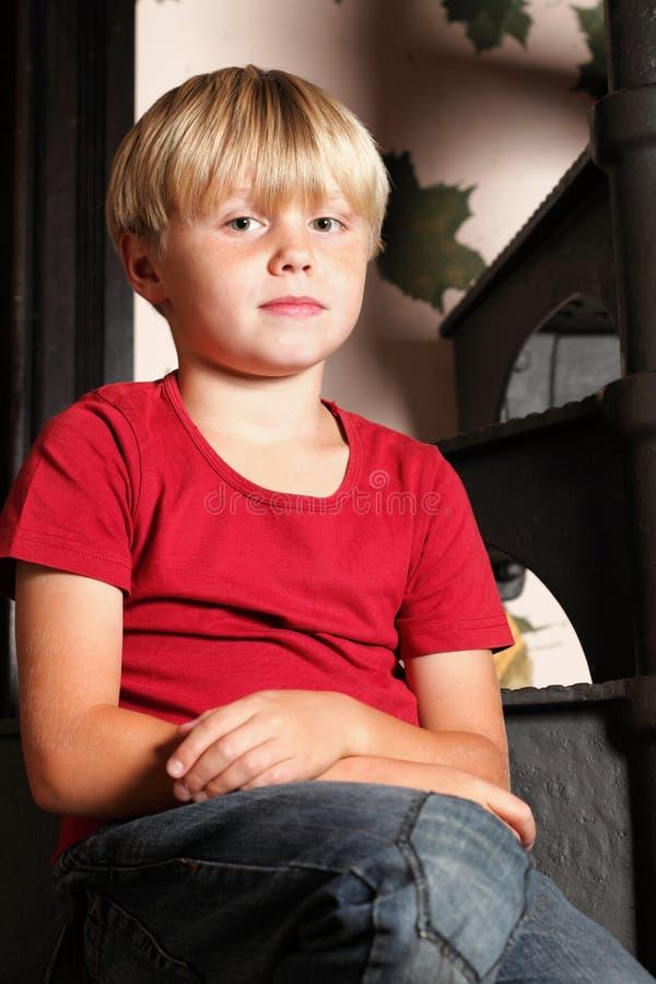 Chłopiec obsiadanie na schodkach obrazy stock