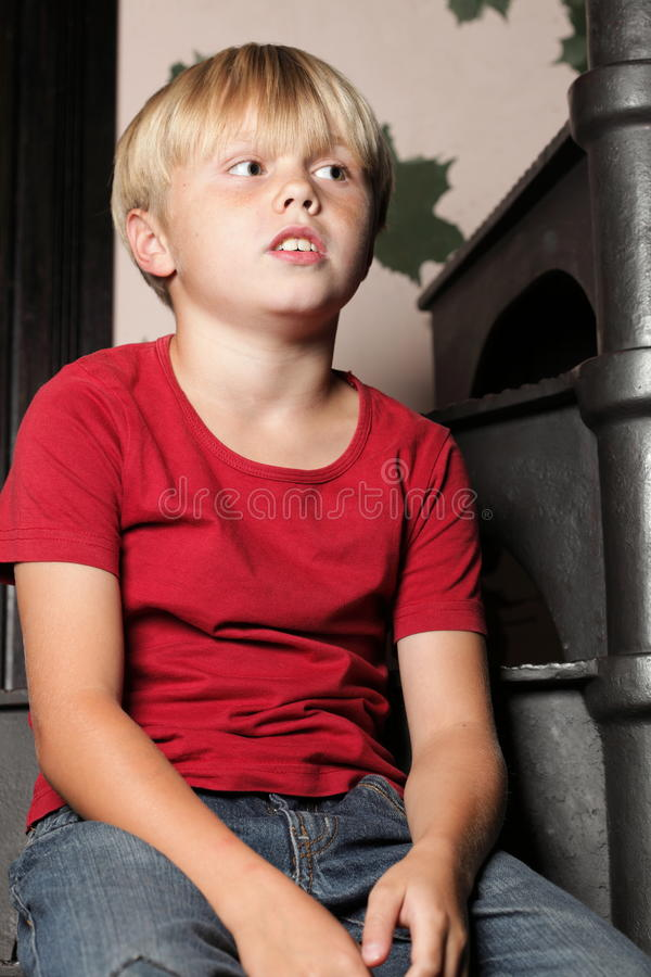 Chłopiec obsiadanie na schodkach fotografia stock