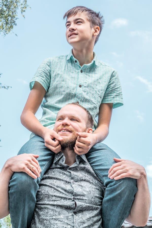 Chłopiec obsiadanie na tata ramionach obraz stock