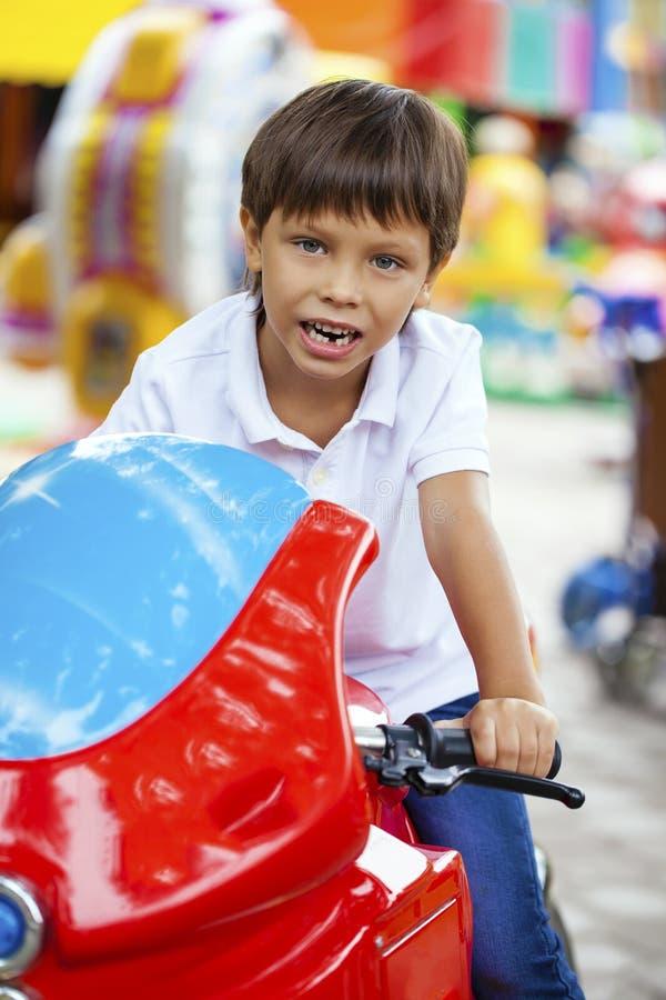 Chłopiec obsiadanie na zabawkarskim motocyklu w parku rozrywki fotografia stock