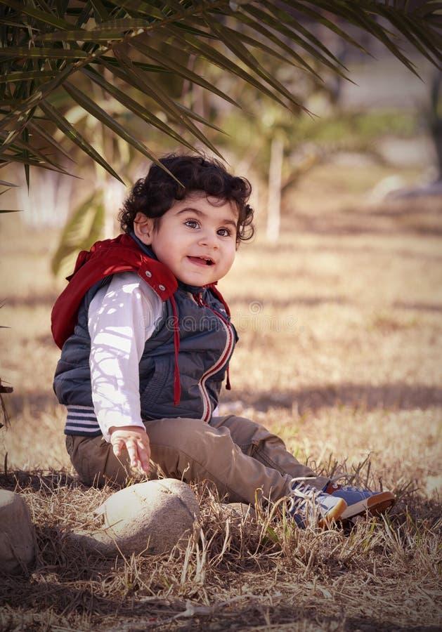 Chłopiec obsiadanie pod drzewkiem palmowym zdjęcie royalty free