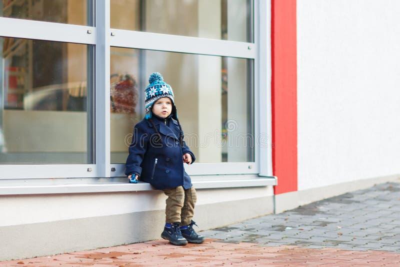 Chłopiec obsiadanie przed dużym okno w mieście, outdoors, obrazy royalty free