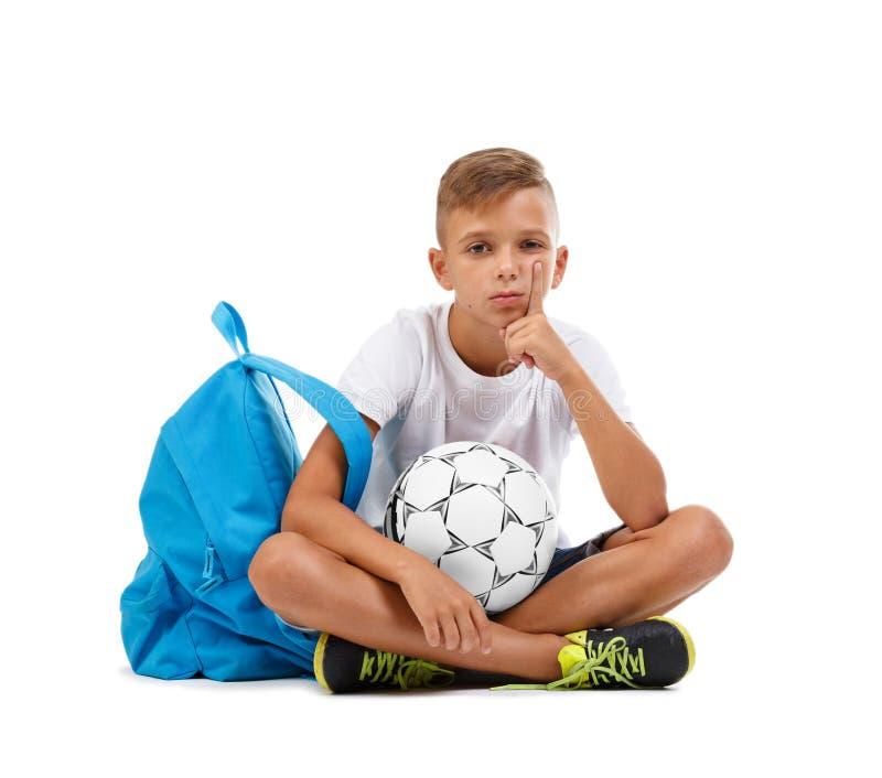Chłopiec obsiadanie w lotosowej pozyci Sportive dzieciak z jaskrawą satchel i piłki nożnej piłką odizolowywającą na białym tle obraz stock
