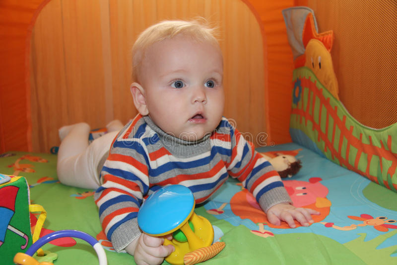Chłopiec obsiadanie w pomarańczowej kojec zdjęcie royalty free