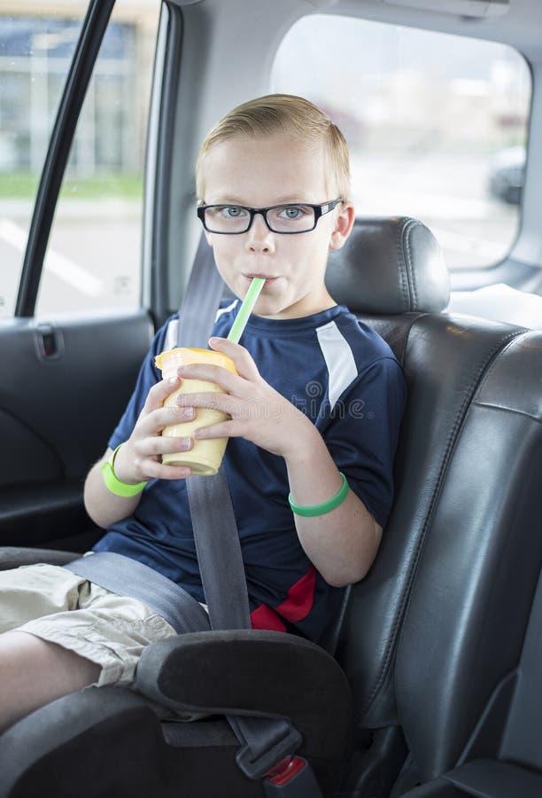 Chłopiec obsiadanie w samochodowym siedzeniu pije smoothie na długiej samochodowej przejażdżce obrazy royalty free
