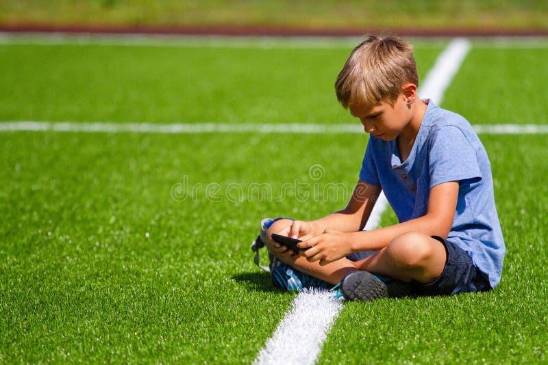 Chłopiec obsiadanie z telefonu komórkowego obsiadaniem w pustym stadionu futbolowego śródpolnym i przyglądającym wideo, pisać na  zdjęcia stock