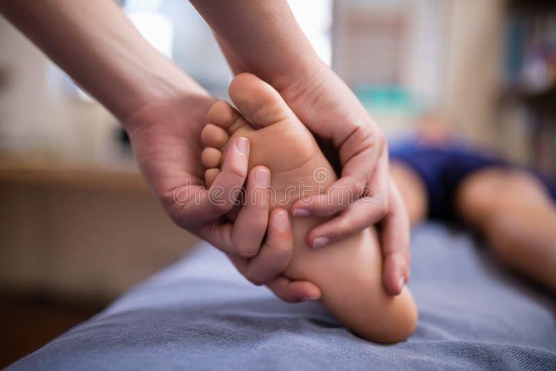 Chłopiec odbiorczy nożny masaż od żeńskiego terapeuta fotografia royalty free