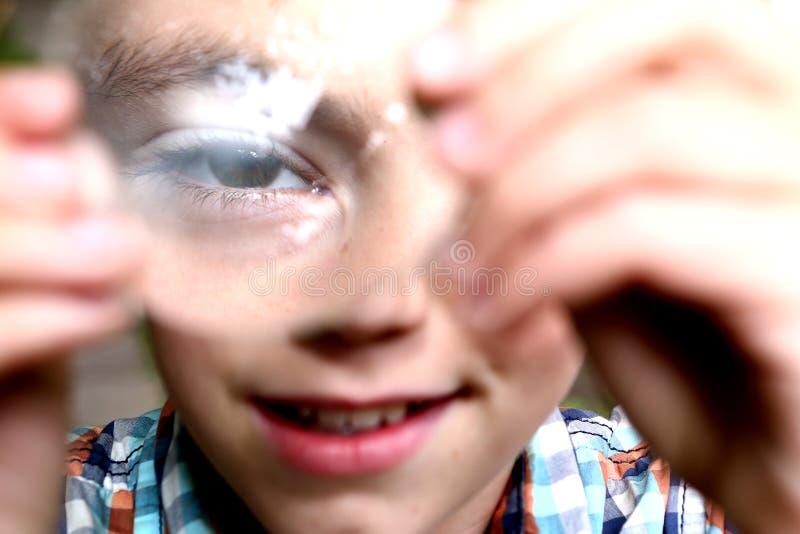 Chłopiec odkrywa właściwości na wypukłym obiektywie zdjęcie stock
