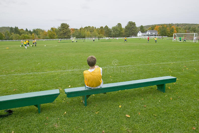 Chłopiec odpoczywa na ławce podczas szkolnej piłki nożnej praktyki, New Hampshire obraz royalty free