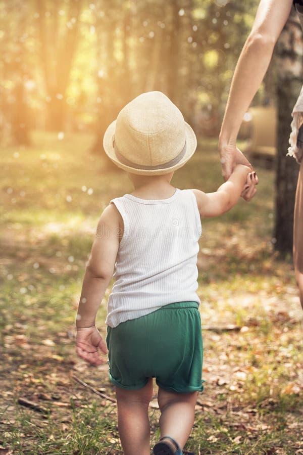Chłopiec odprowadzenie z mamą w parku zdjęcie stock