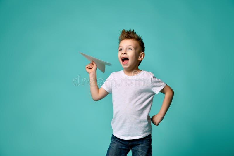 Chłopiec odważny pilotowy bohater gotowy wszczynać samolotu papierowych spojrzenia do nieba i krzyków energiczny Odlot obraz royalty free