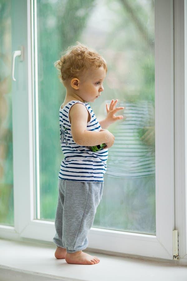 Chłopiec ogląda deszcz przez okno zdjęcia stock