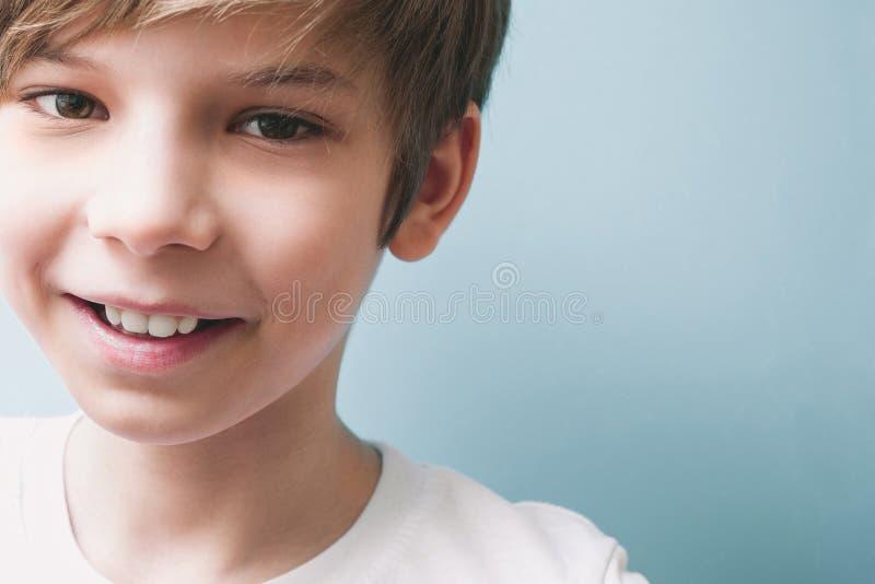 Chłopiec ono uśmiecha się na błękitnym tle fotografia stock