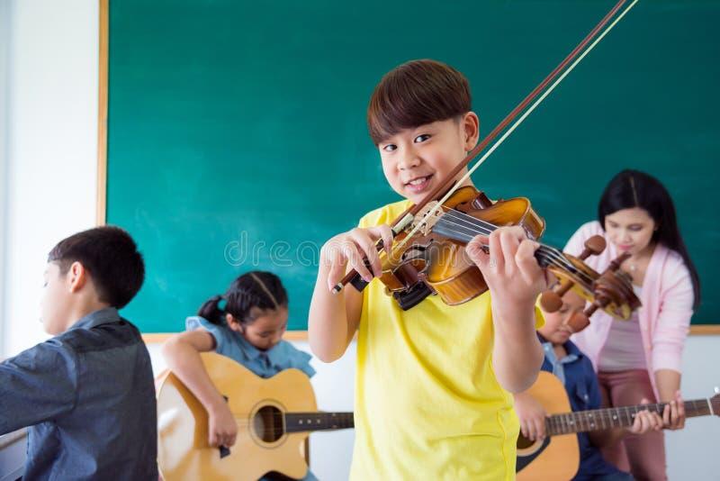Chłopiec ono uśmiecha się podczas gdy bawić się skrzypce w muzycznej klasie zdjęcia royalty free