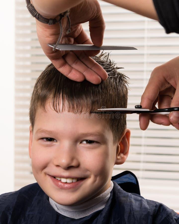 Chłopiec ono uśmiecha się podczas haircutting procesu fryzjerem obrazy stock