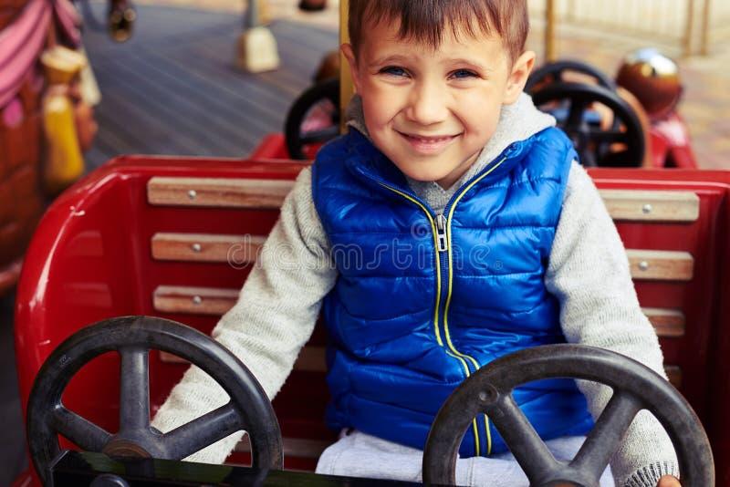 Chłopiec ono uśmiecha się w zabawkarskim samochodzie zdjęcia stock
