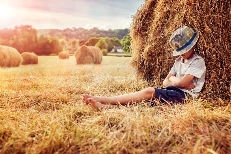 Chłopiec opiera i śpi przeciw haystack przy zmierzchem zdjęcie stock