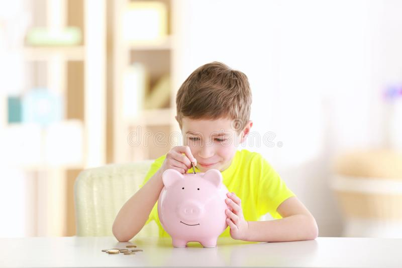 Chłopiec oszczędzania monety w prosiątko banku zdjęcia royalty free