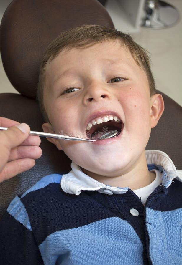 Chłopiec otwiera jego usta szerokiego podczas inspekci oralny cavi zdjęcia royalty free