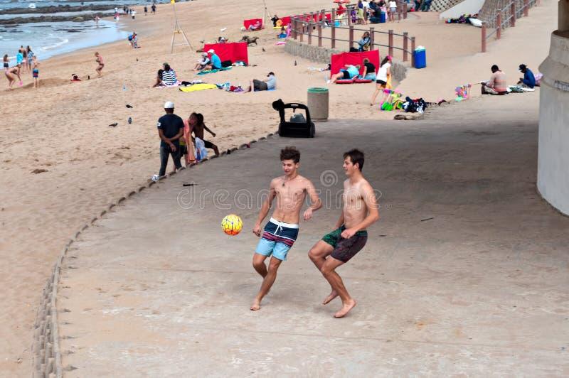 Chłopiec płaci plażową piłkę nożną blisko milenium latarni morskiej w Umhlanga skałach i mola obraz stock