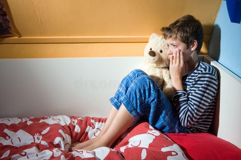 Chłopiec płacz na jego łóżku fotografia royalty free