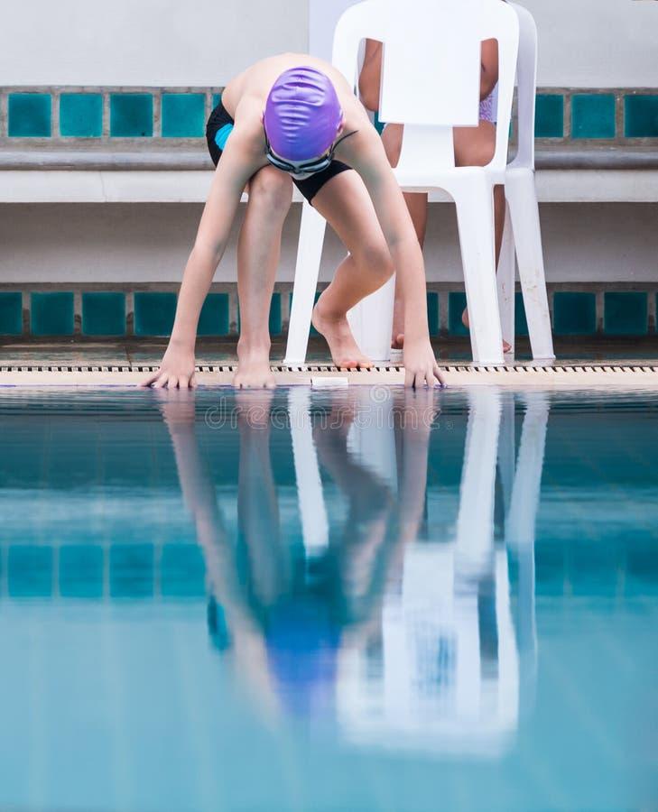 Chłopiec pływaczka dostaje przygotowywający skakać w basenie fotografia royalty free