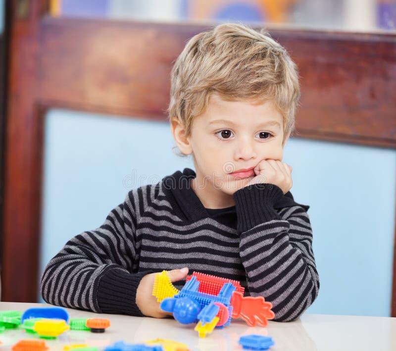 Chłopiec Patrzeje Daleko od W Preschool Z blokami fotografia stock
