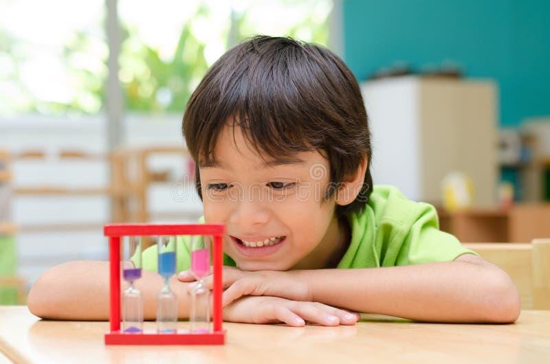 Chłopiec patrzeje hourglass w klasie obrazy stock
