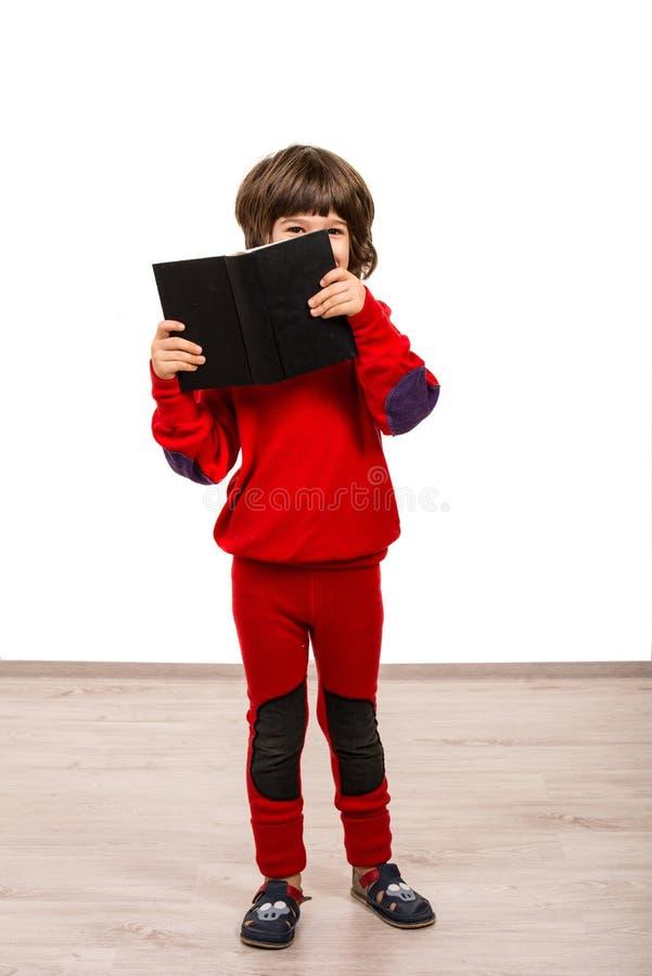 Chłopiec patrzeje nad ono uśmiecha się i książką obrazy royalty free