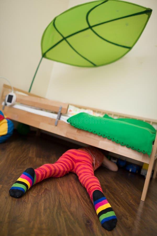 Chłopiec patrzeje pod łóżkiem w czerwieni paskował spodnia i skarpety Zabawka pod łóżkiem zdjęcia stock