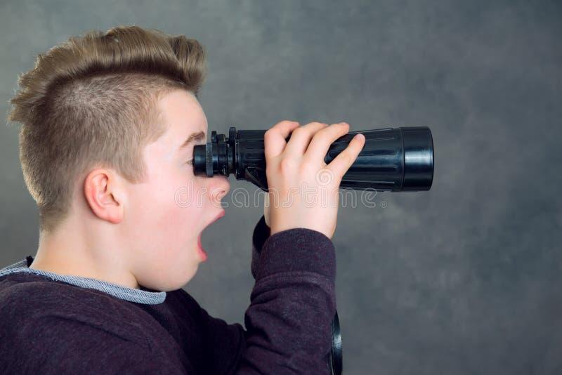 Chłopiec patrzeje przez lornetki fotografia stock