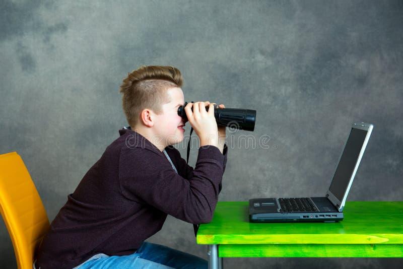 Chłopiec patrzeje przez lornetki przy komputerem obraz stock