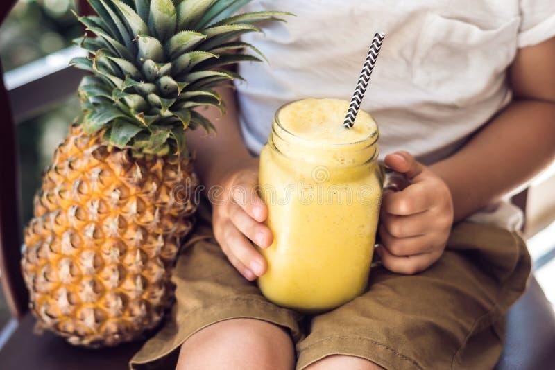 Chłopiec pije ananasowego smoothie na tarasie obraz royalty free