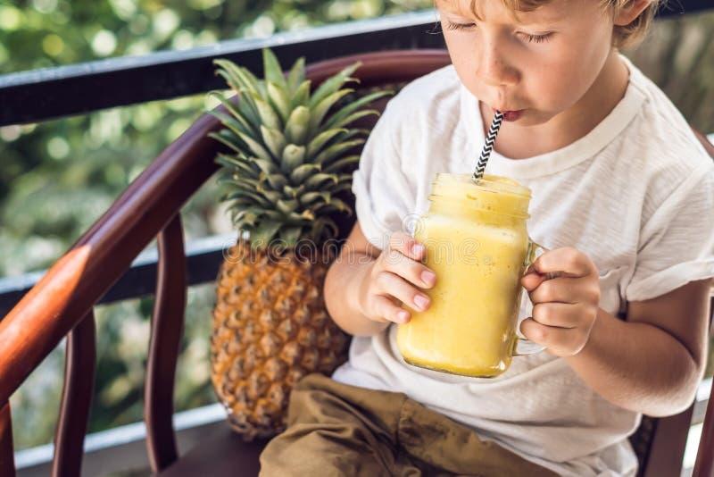 Chłopiec pije ananasowego smoothie na tarasie zdjęcie royalty free