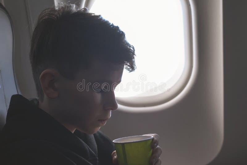 Chłopiec pije od papierowej filiżanki siedzi blisko samolotowego okno podczas lotniczego lota Jedzenie słuzyć na pokładzie fotografia stock
