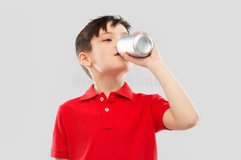 Chłopiec pije sodę od blaszanej puszki w czerwonej koszulce obrazy royalty free