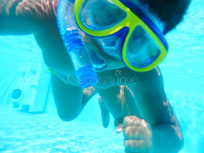 Chłopiec pikowanie przy basenem z maską zdjęcia royalty free