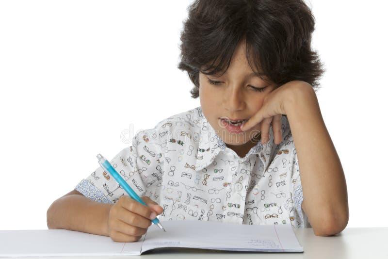 Chłopiec pisze w jego ćwiczenie książce zdjęcia royalty free