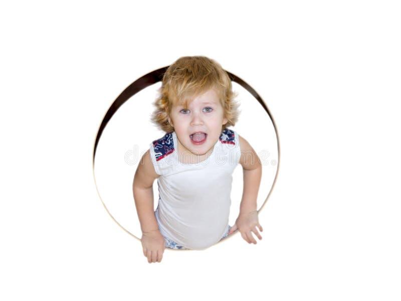 Chłopiec połówka wspinająca się za round okno w i uśmiechy contentedly wyprostowywamy w ramę zdjęcie royalty free