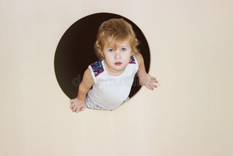 Chłopiec połówka wspinająca się za round okno w i uśmiechy contentedly wyprostowywamy w ramę zdjęcia royalty free