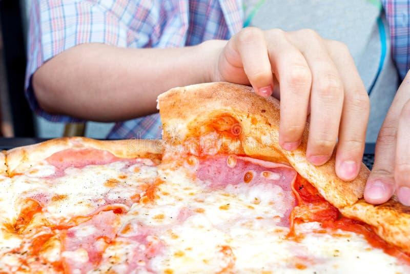 Chłopiec podnosi w górę plasterka pizza obrazy stock