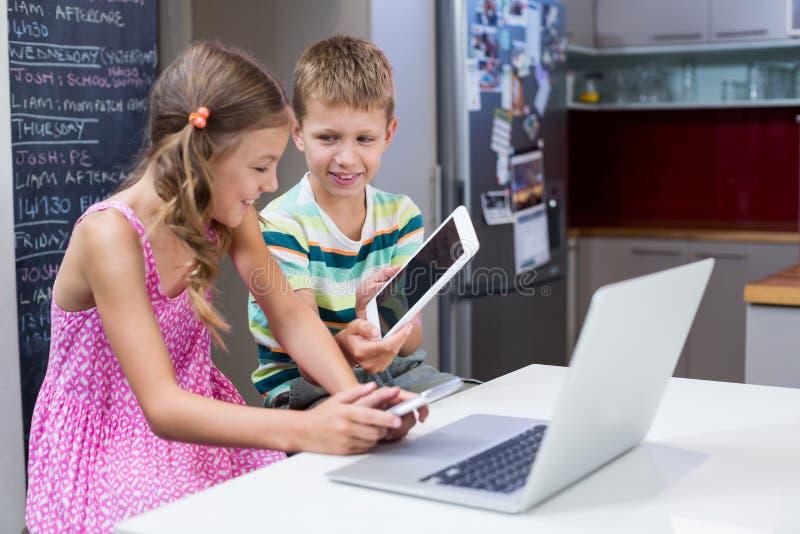 Chłopiec pokazuje cyfrową pastylkę dziewczyna w kuchni fotografia royalty free