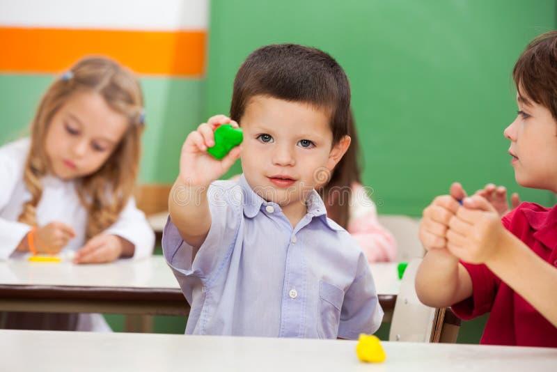 Chłopiec Pokazuje glinę Przy sala lekcyjną obrazy stock