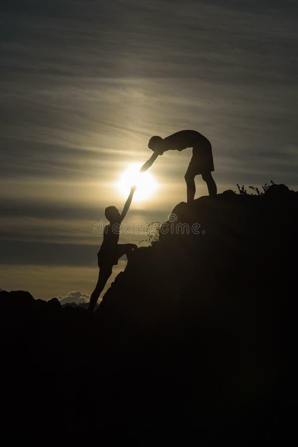 Chłopiec pomagać ciągnąć wpólnie wspinać się obraz stock