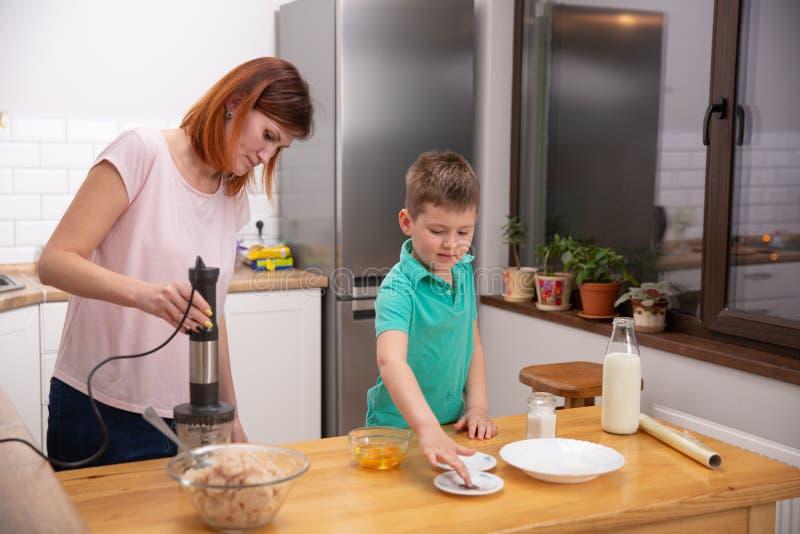 Chłopiec pomaga jego matki z kucharstwem w kuchni obrazy royalty free