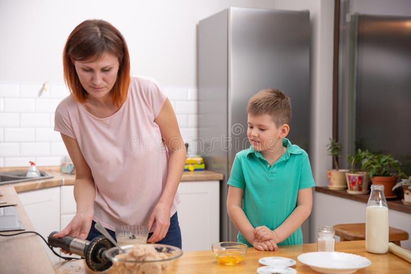 Chłopiec pomaga jego matki z kucharstwem w kuchni obraz royalty free