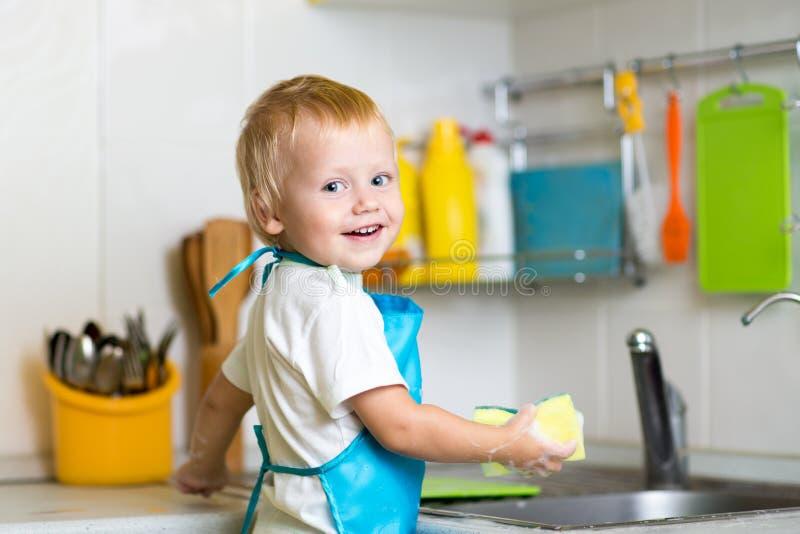 Chłopiec pomaga macierzystym domycie naczyniom w kuchni zdjęcie royalty free