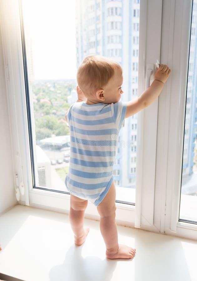 Chłopiec pozycja na nadokiennym parapecie i ciągnięcie nadokiennej rękojeści Conc, zdjęcie stock